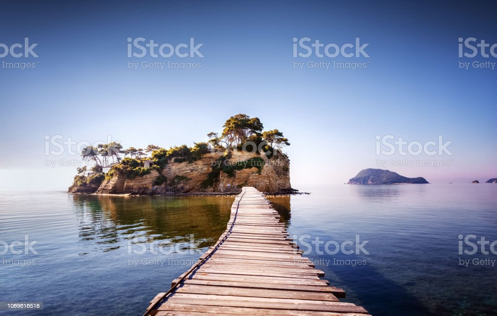 Picturesque view on lonely island Cameo in Greece, part of island Zakinthos or Zante, Port Sostis. Dramatic scenery of solitude island in ocean with wooden path. Iconic landmark on Zakinthos island. stock photo