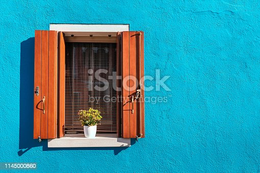 Picturesque window in blue colorful house as design concept