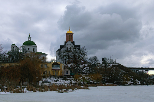 Bila Tserkva, Ukraine-February 28, 2021:Picturesque winter landscape view of Church of St. George and Church of St. Ivan the Baptist in Bila Tserkva. Frizzed Ros River in foreground. Cloudy winter day