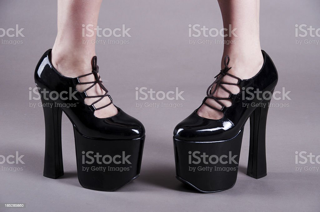 Pidgeon-toed feet in tall black platform shoes stock photo