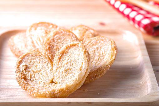 Pie a butterfly, heart shaped patty crispy on wooden plate