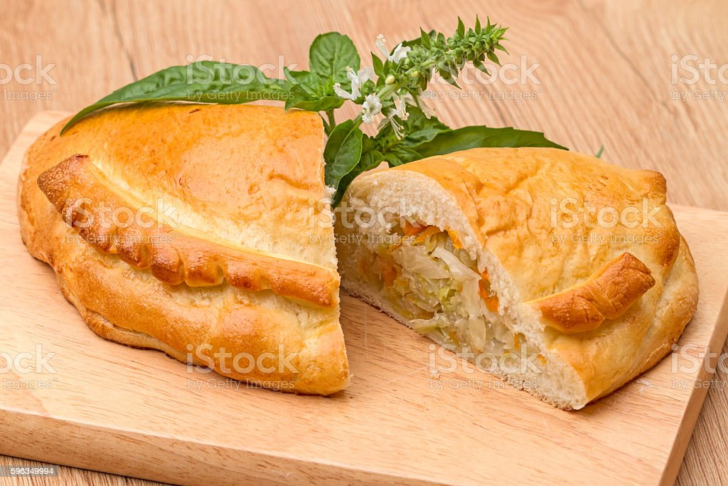 Pie with cabbage and a sprig of basil Lizenzfreies stock-foto