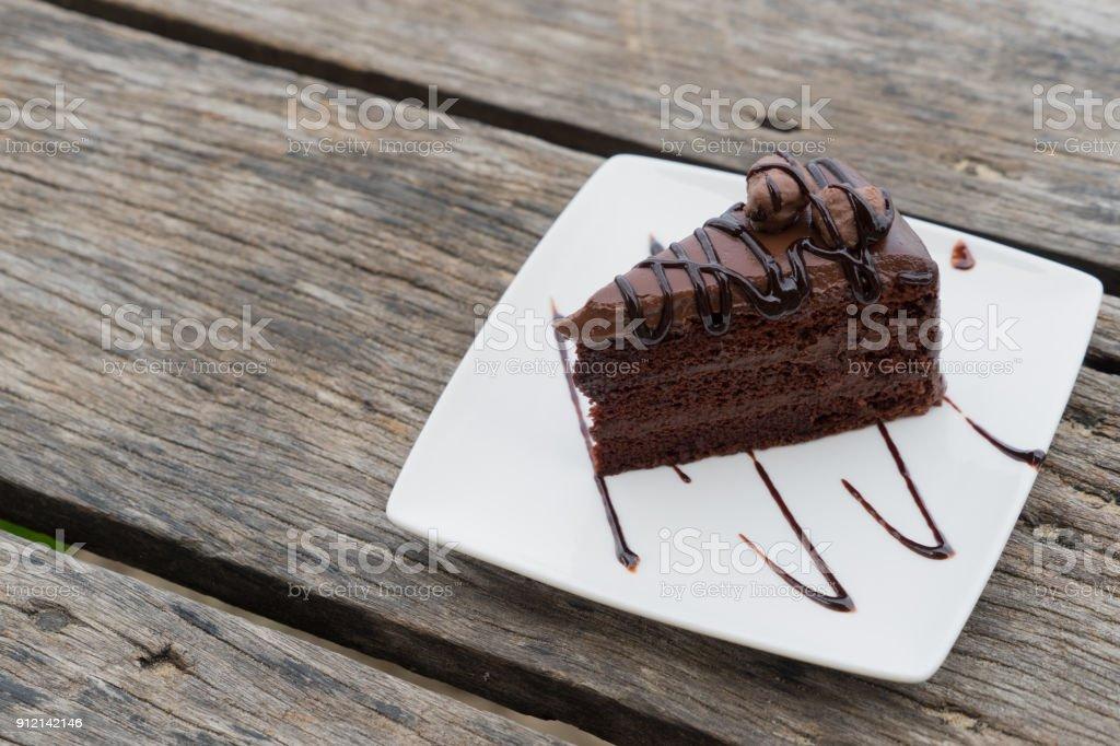 peça chocolate bolo caminho chapa branca de madeira mesa de trabalho - foto de acervo