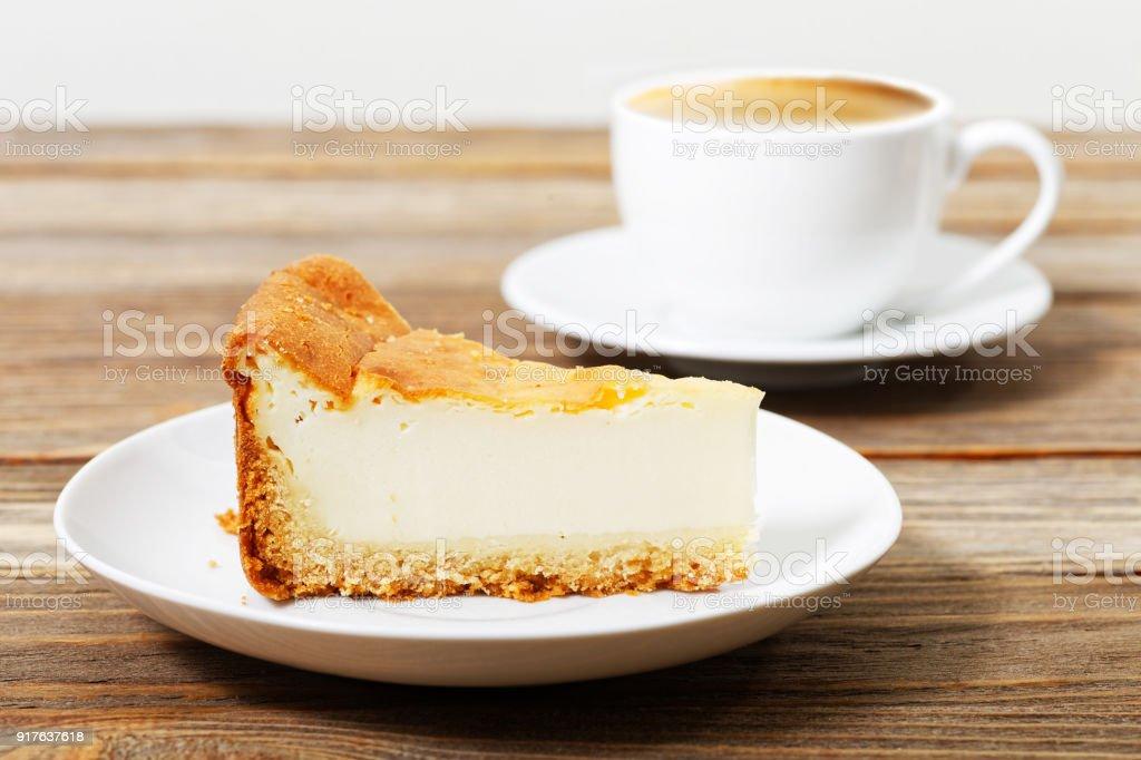 Stück Käsekuchen auf einem weißen Untertasse und Tasse Kaffee – Foto