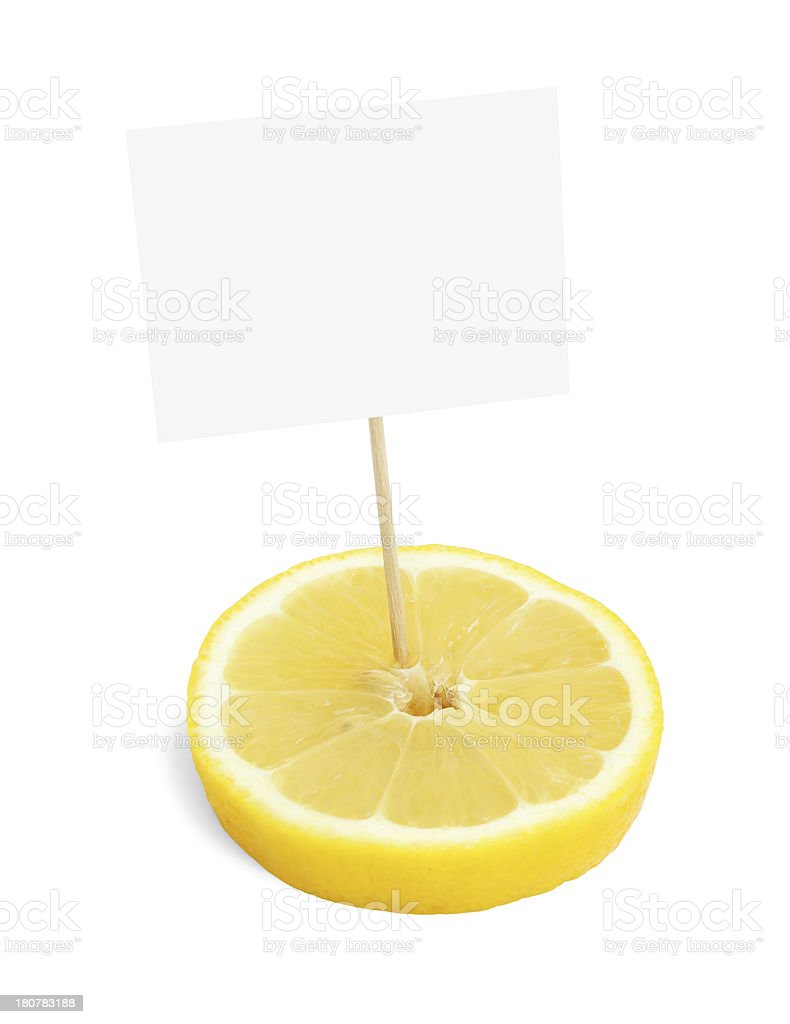 Piece of a fresh lemon with blank cardboard information tag royalty-free stock photo