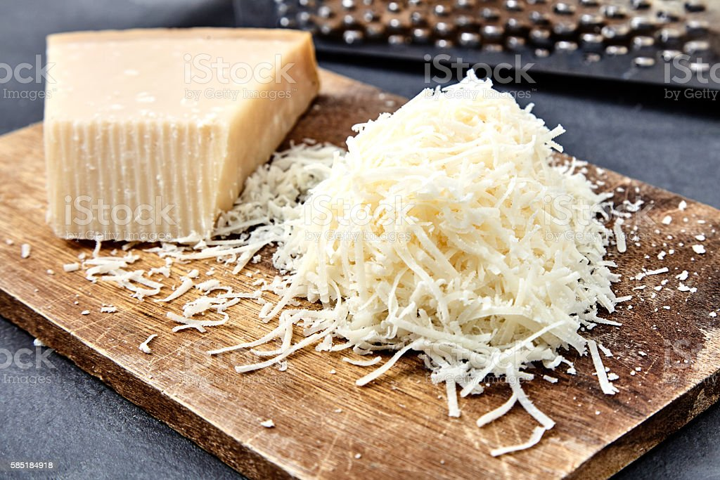 Piece of a parmesan and grated cheese stock photo