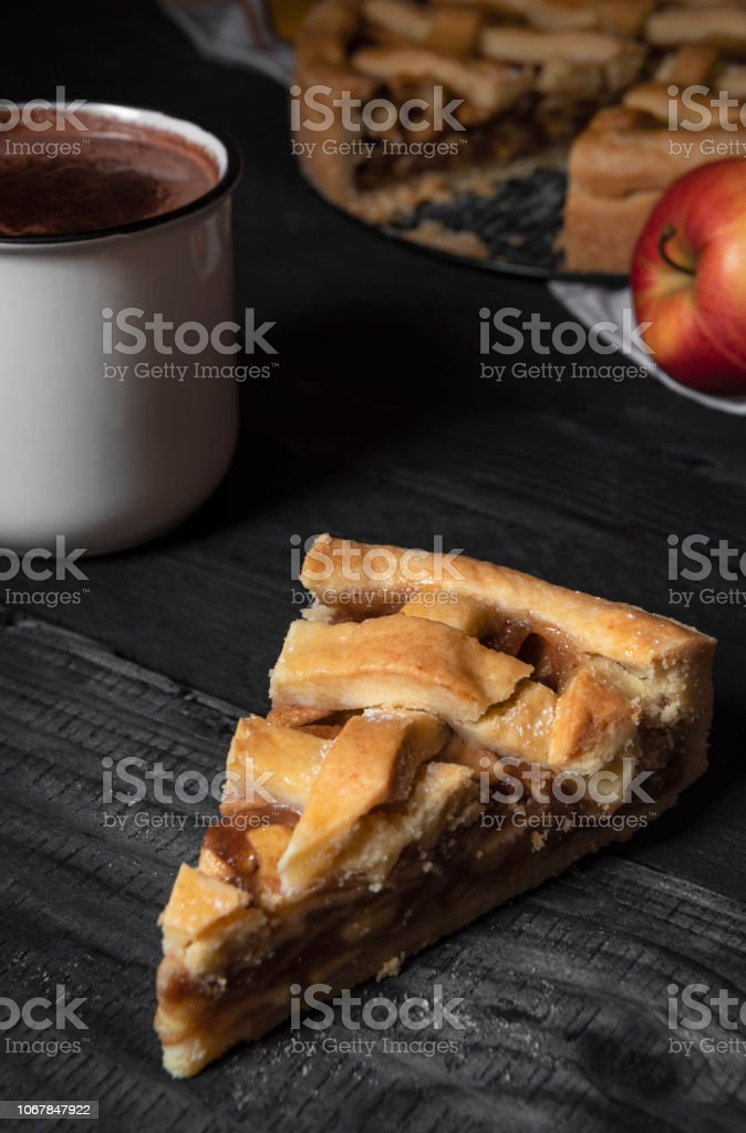 Vertical image with a slice of apple pie on a rustic wooden table, a...