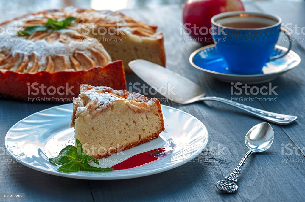 Piece of apple pie on plate with jam, tea cup stock photo