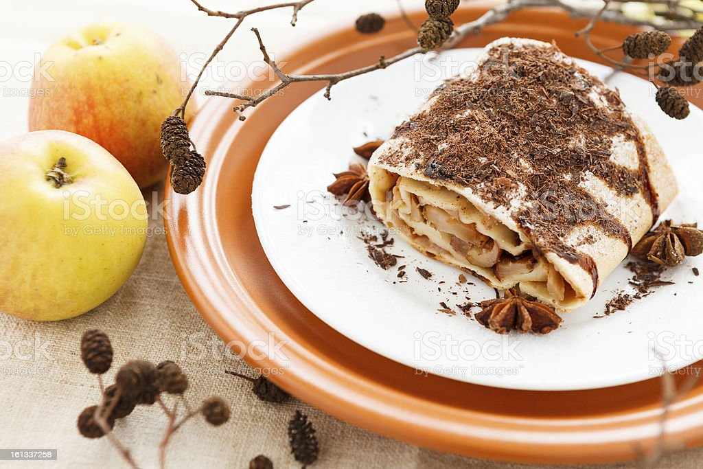 Piece of apple pie strewn grated chocolate and two apples royalty-free stock photo