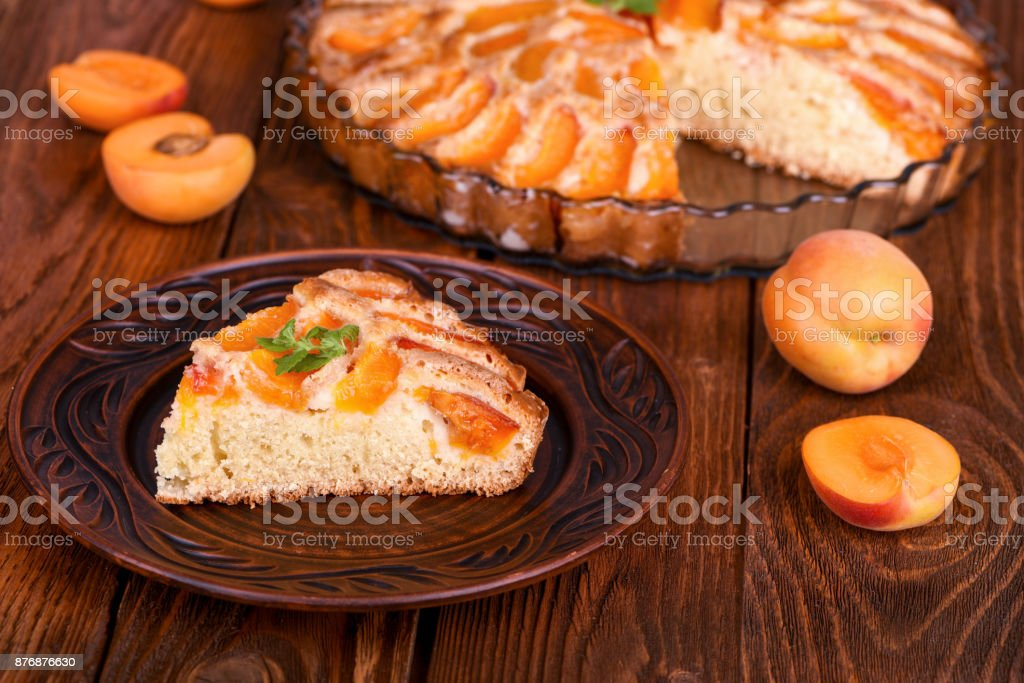 Piece of apricot cake on wooden table. stock photo