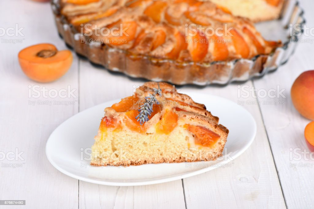 A piece of apricot pie decorated with a sprig of lavender. stock photo