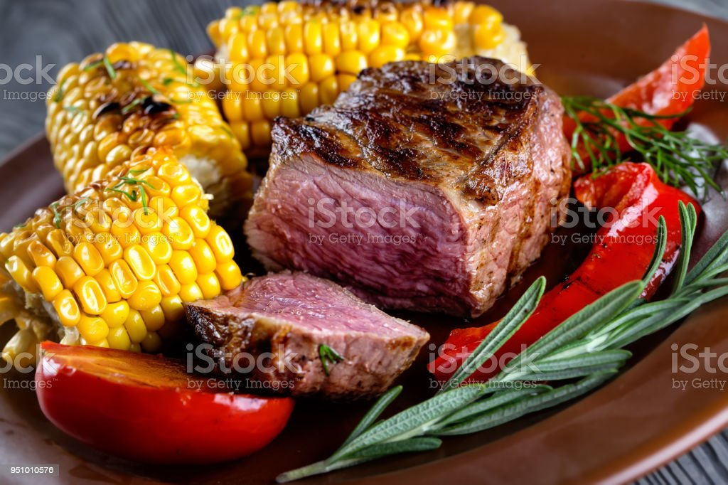 A piece of baked meat with cut slice on clay plate stock photo