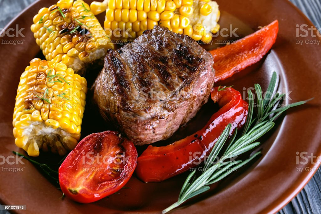 Piece of baked meat with vegetables and marinated on plate stock photo