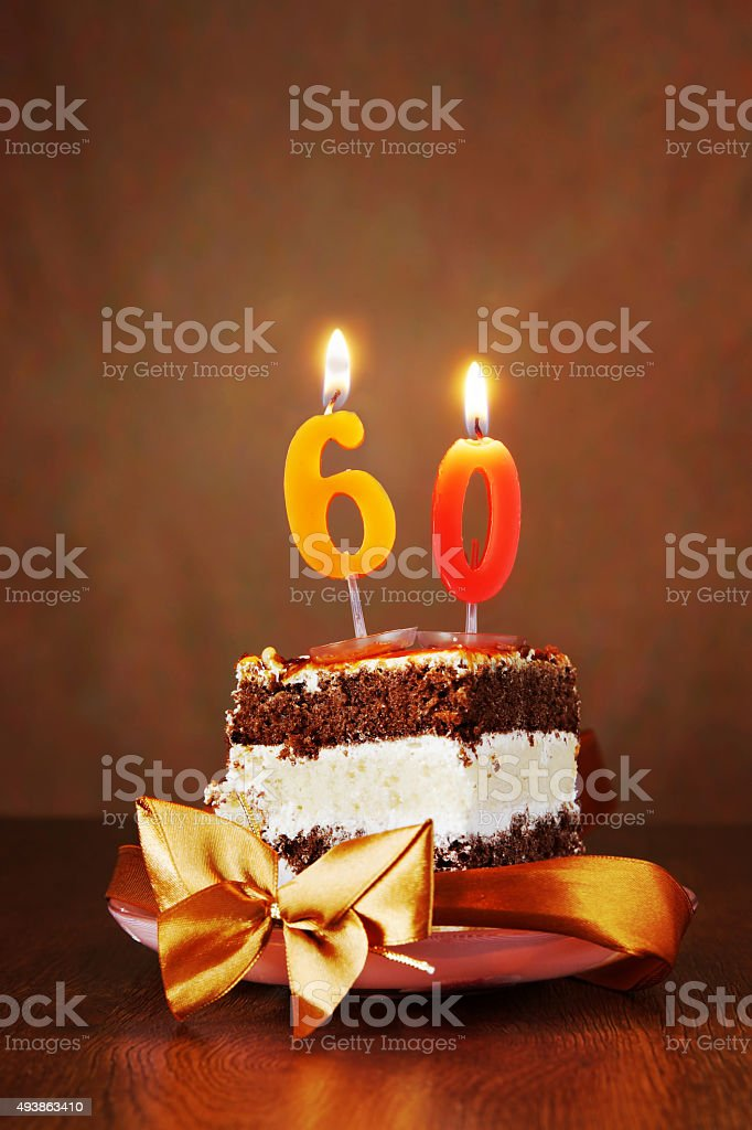 Piece of Birthday Cake with Burning Candle as Number Sixty stock photo