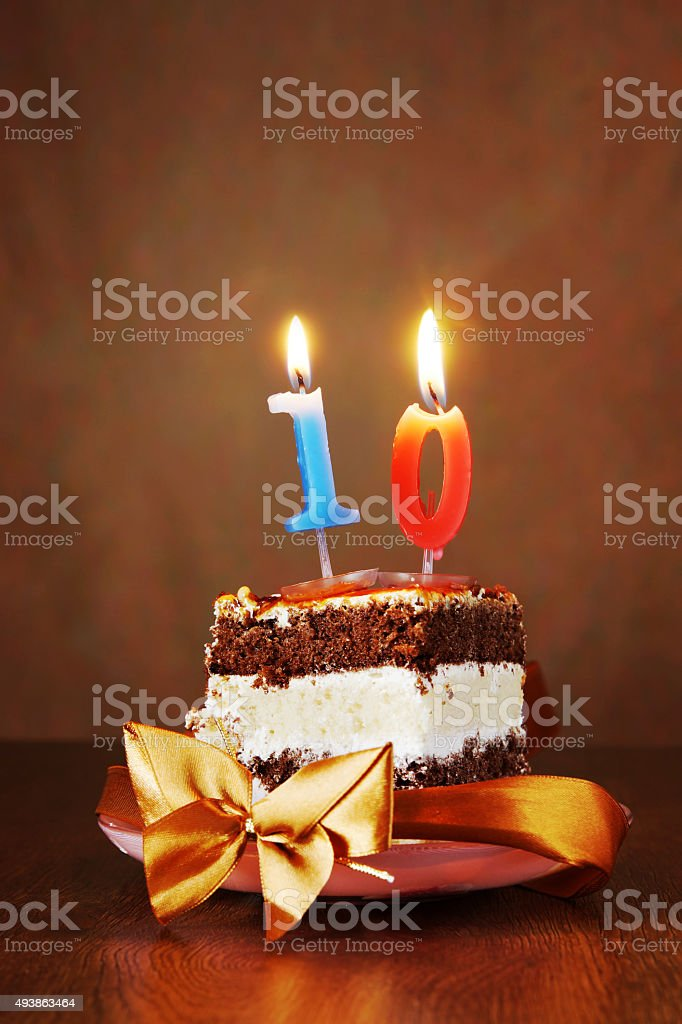 Piece of Birthday Cake with Burning Candle as Number Ten stock photo