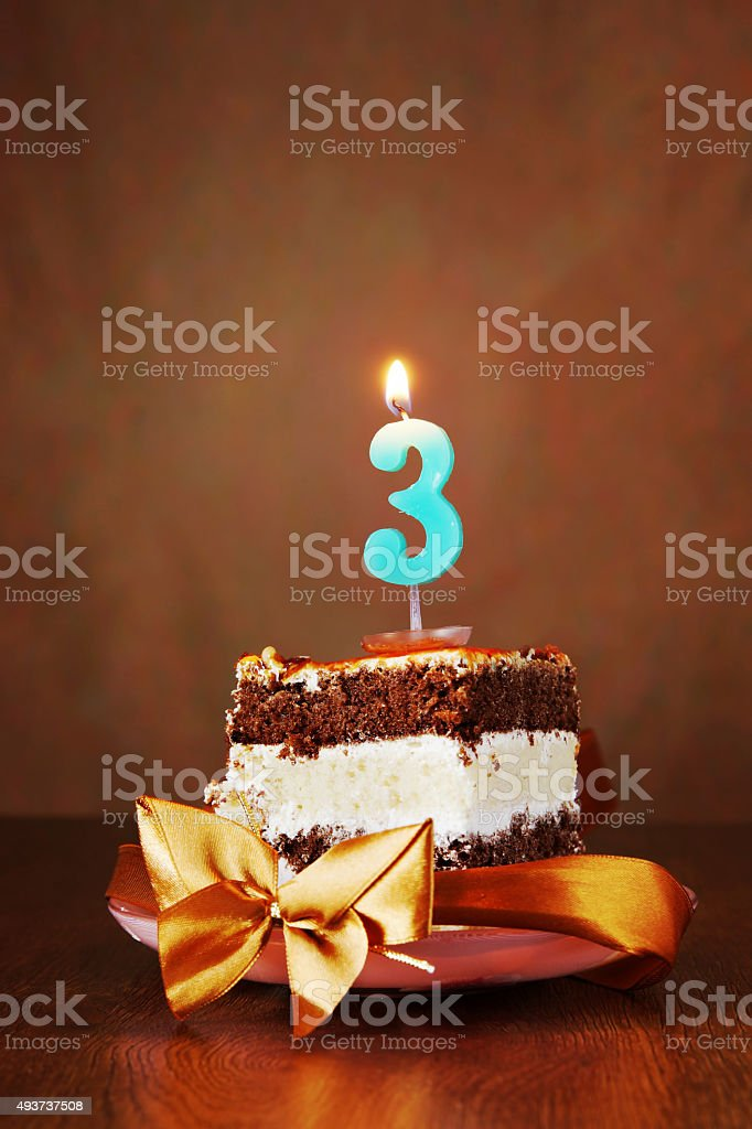 Piece of Birthday Cake with Burning Candle as Number Three stock photo