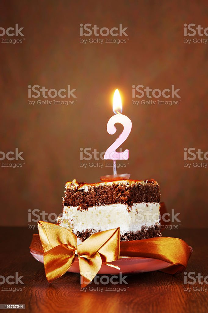 Piece of Birthday Cake with Burning Candle as Number Two stock photo