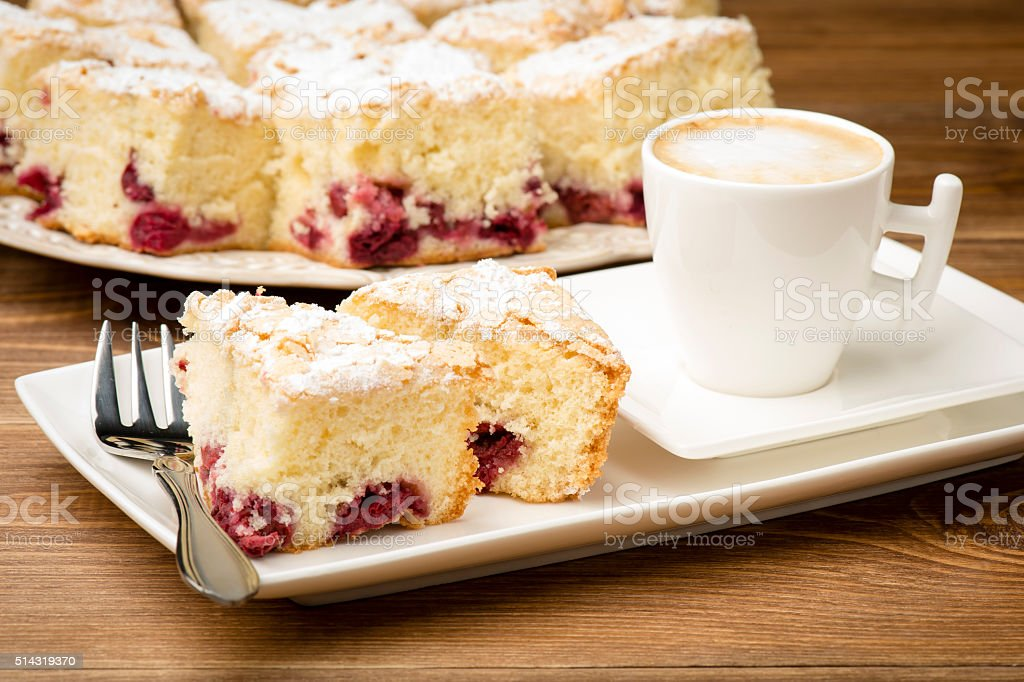 Piece of biscuit with cherry and a cup of coffee. stock photo