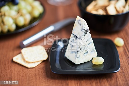 A piece of blue cheese is on a black plate