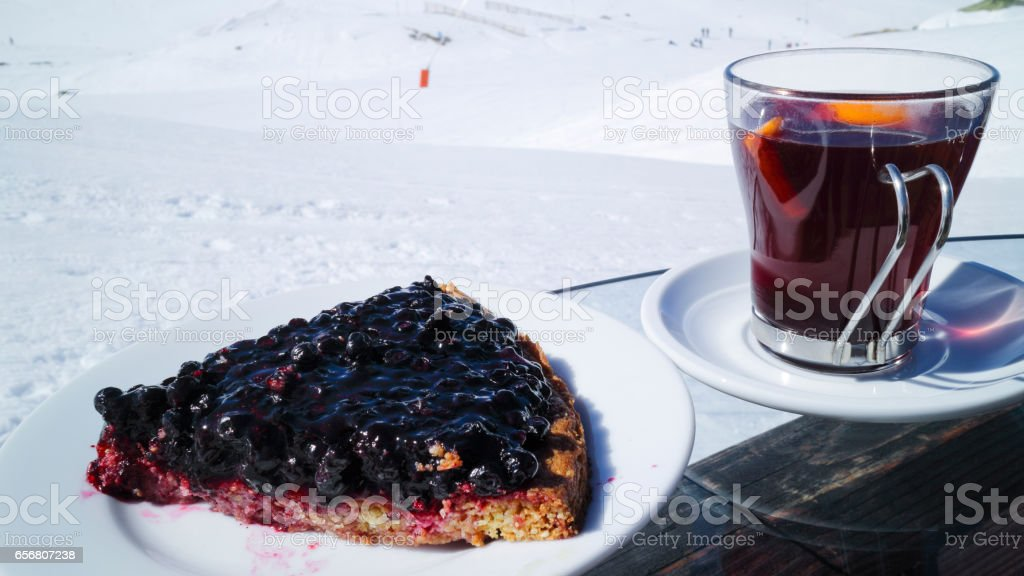 Piece of blueberry cake, hot red wine in a glass, apres ski on a slope in French Alps stock photo