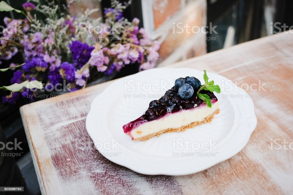 A piece of blueberry cheesecake on wooden table. stock photo