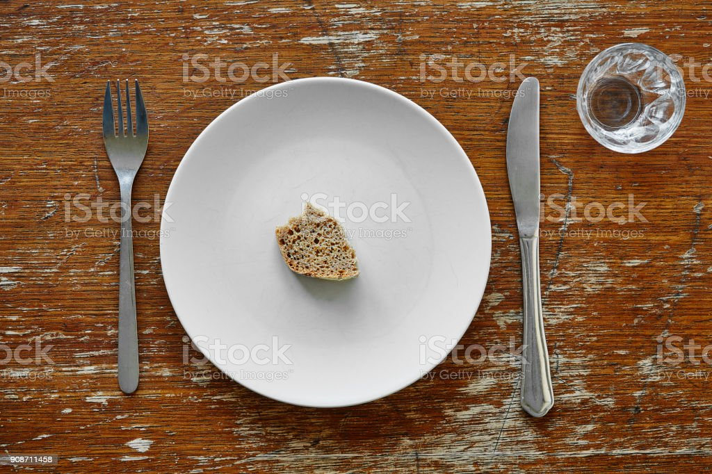 piece of bread on plate metaphor for hunger stock photo