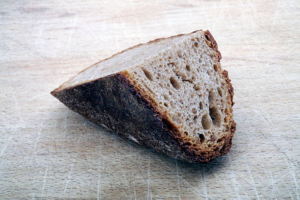 Piece of brown bread Piece of brown bread cusp stock pictures, royalty-free photos & images