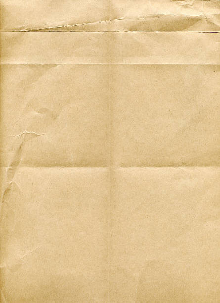A piece of brown paper with fold marks and creases stock photo