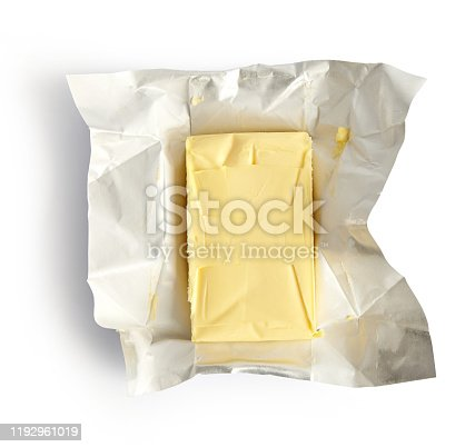 Piece of butter isolated on white background, top view