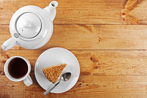 piece of cake and tea pot on wooden table