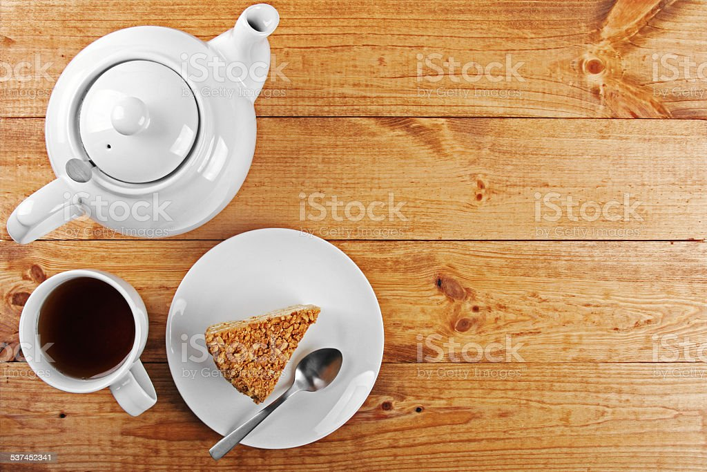 piece of cake and tea pot on wooden table stock photo