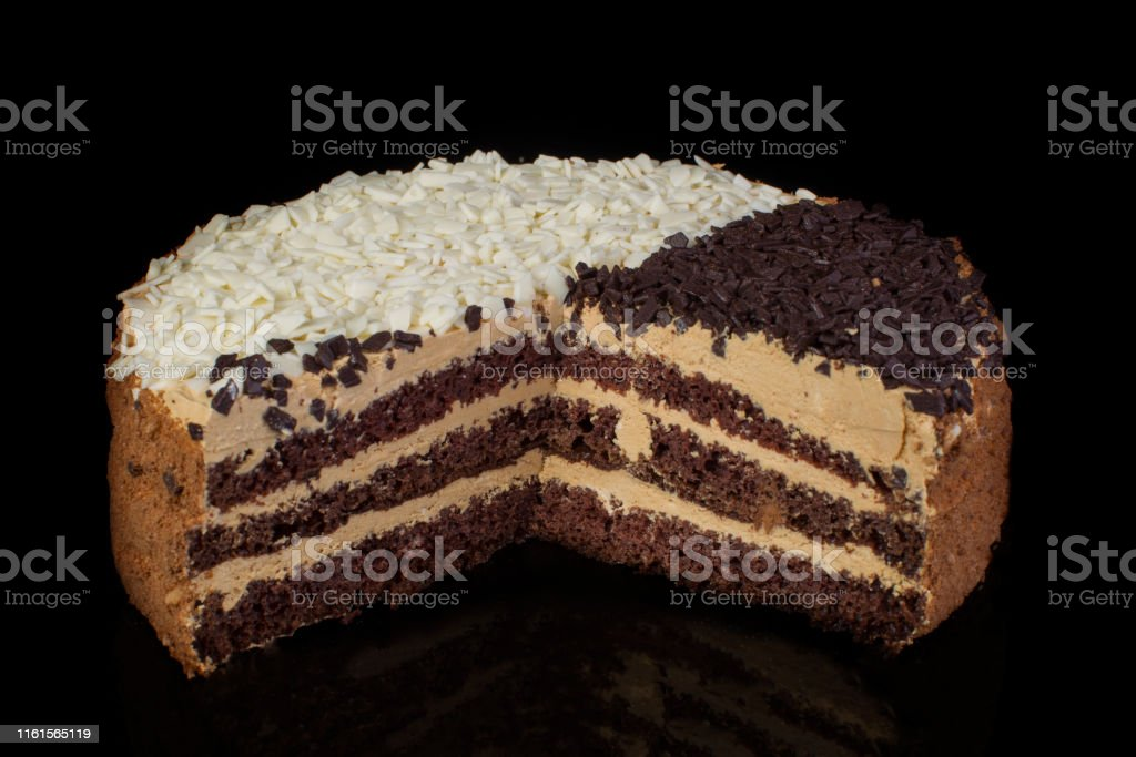 Piece of cake with white and black chocolate on a black...