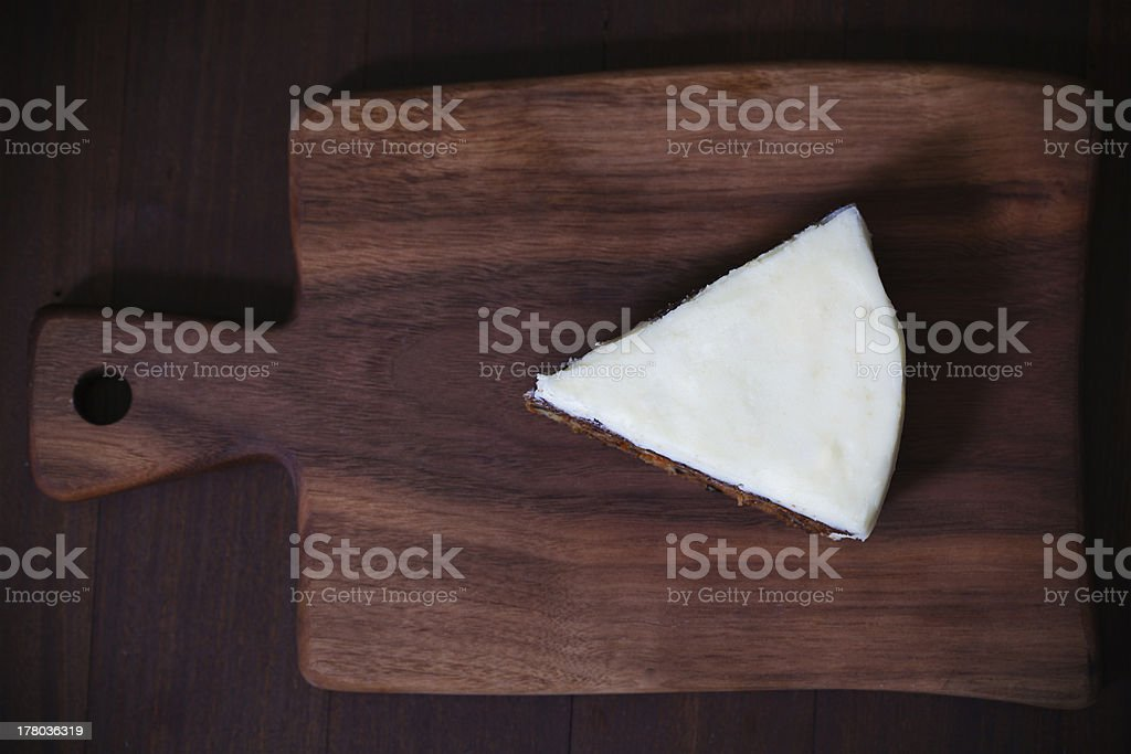 Piece of cake with white marzipan icing, wooden board royalty-free stock photo