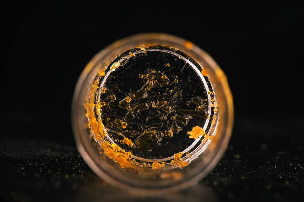 Piece of cannabis oil concentrate aka shatter isolated on a container stock photo