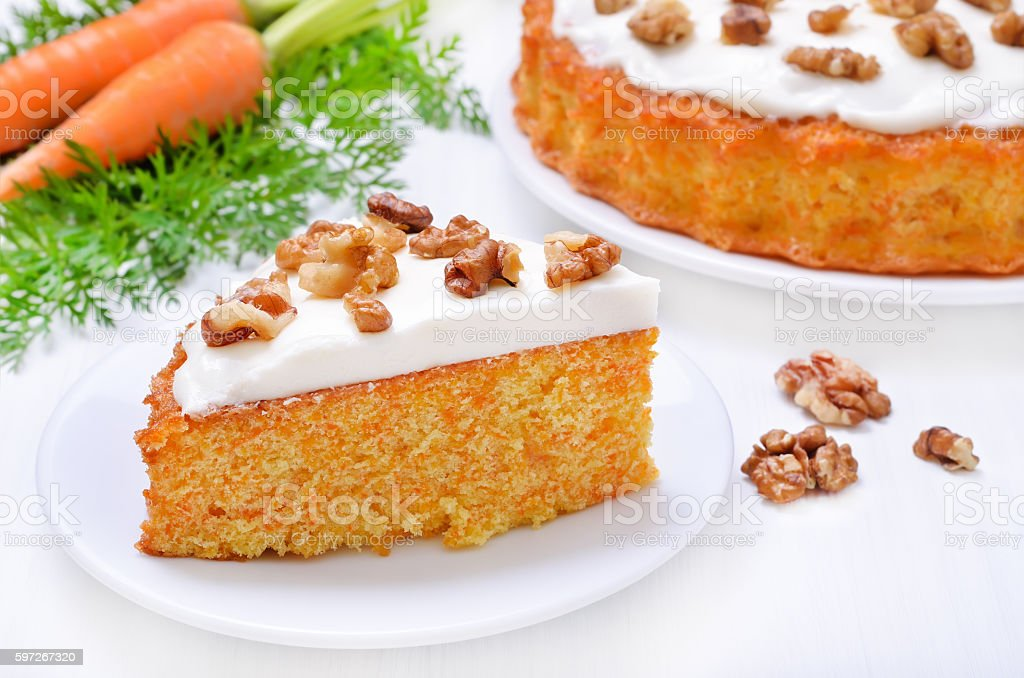 Piece of carrost cake with icing decorated walnut Lizenzfreies stock-foto