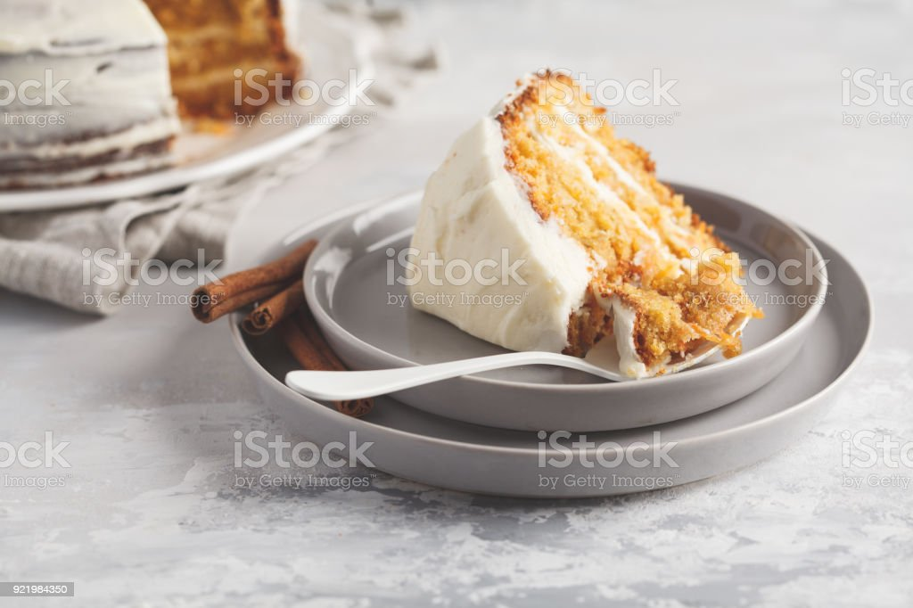 Piece of carrot homemade cake with white cream (cream cheese) on a gray background. Festive dessert concept. stock photo