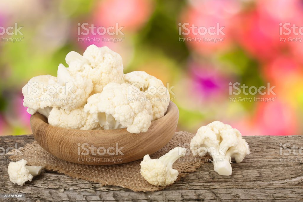 Piece of cauliflower in bowl on wooden table with blurred garden background stock photo