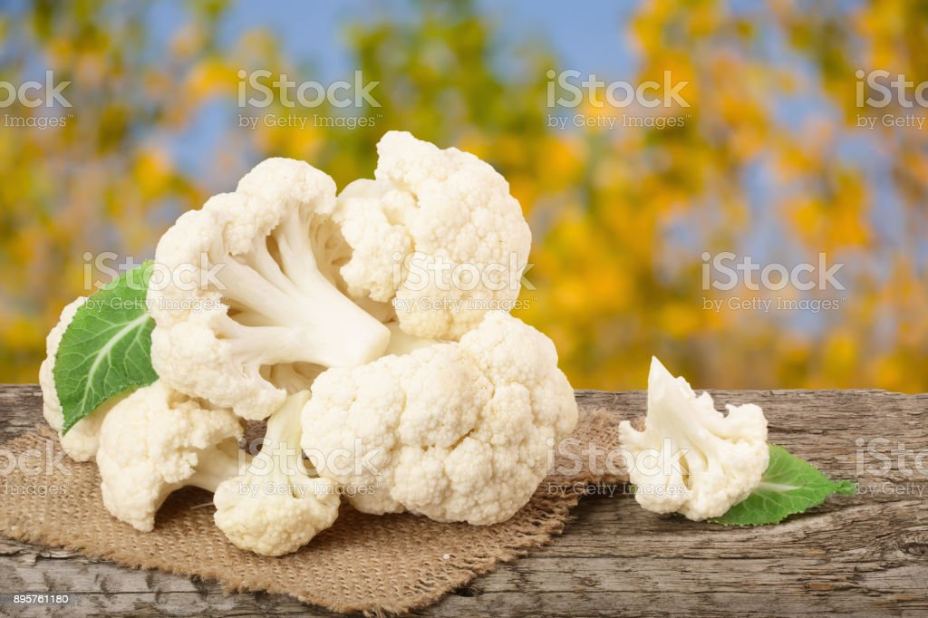 Piece of cauliflower on wooden table with blurred garden background stock photo