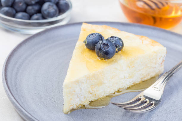 Piece of cheese casserole or cheesecake, garnished with blueberry and honey, on a gray plate, horizontal stock photo