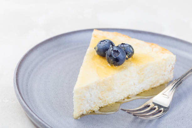 Piece of cheese casserole or cheesecake, garnished with blueberry and honey, on  gray plate, horizontal stock photo