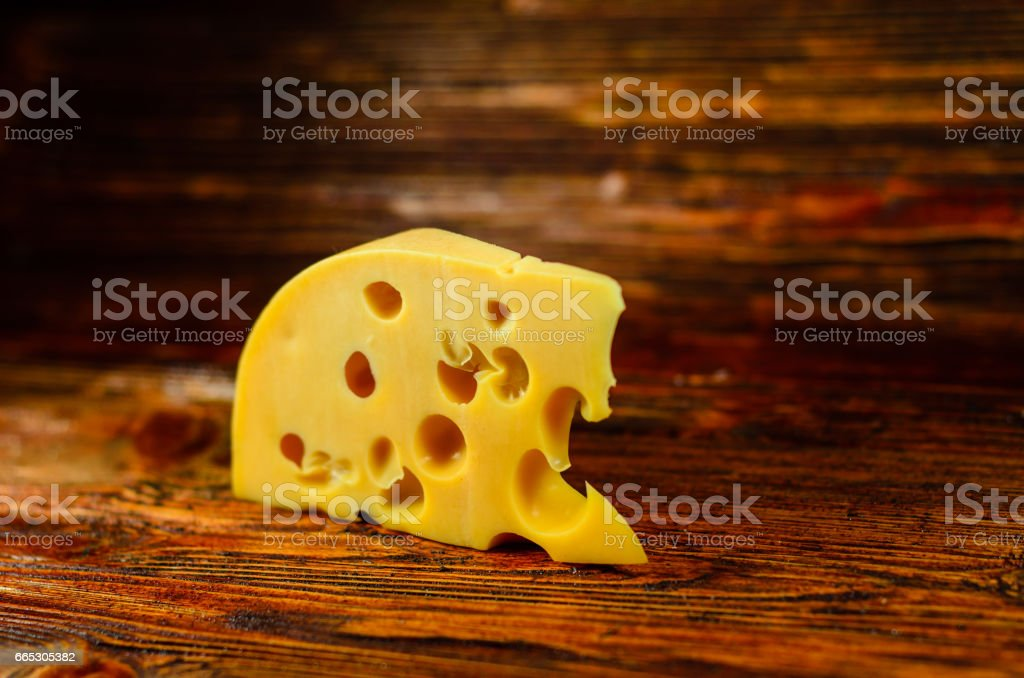 Piece of cheese on wooden table stock photo