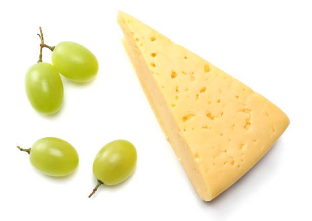 stück käse mit trauben, die isoliert auf weißem hintergrund - traubensorten stock-fotos und bilder