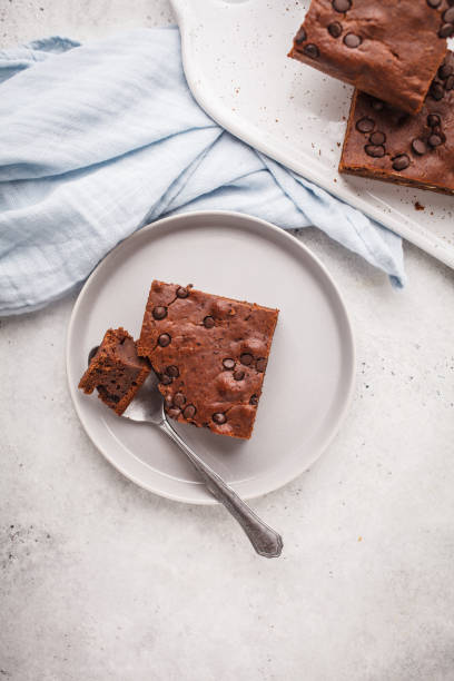Piece of chocolate vegan cake with chocolate drops and nuts, top view. stock photo