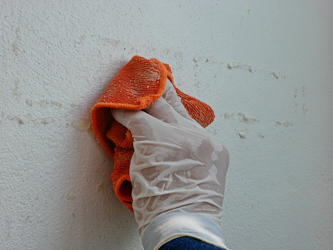A piece of cloth, soaked with thinner, in a hand of a painter being used to remove sticky rough glue and tape remain on the old concrete wall, as a preparation before starting the paint the house