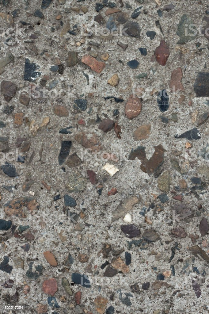 A piece of concrete wall with pebbles stock photo
