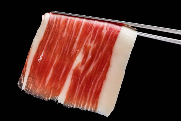 Piece of cured ham on tweezer. stock photo