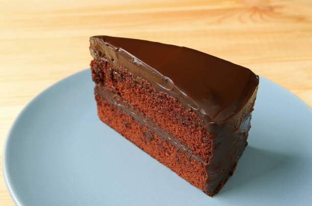 Piece of Delectable Chocolate Layer Cake Served on Blue Plate on the Wooden Table - fotografia de stock
