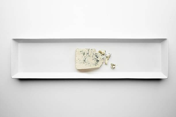 Piece of gorgonzola isolated on white plate stock photo