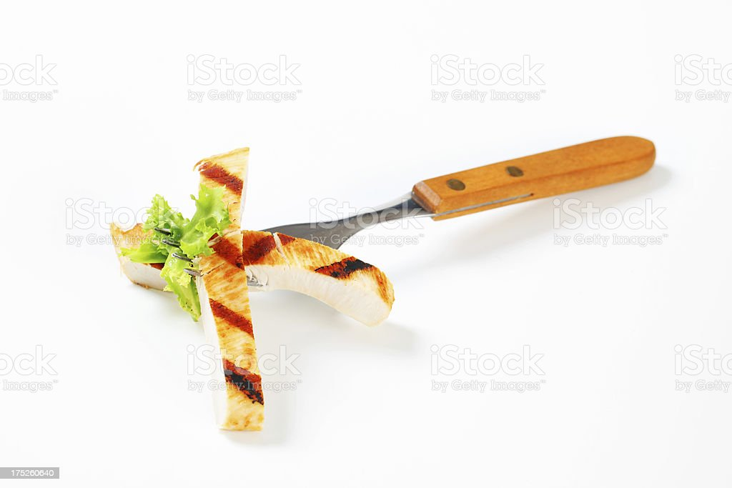 Piece of grilled turkey steak on a fork royalty-free stock photo