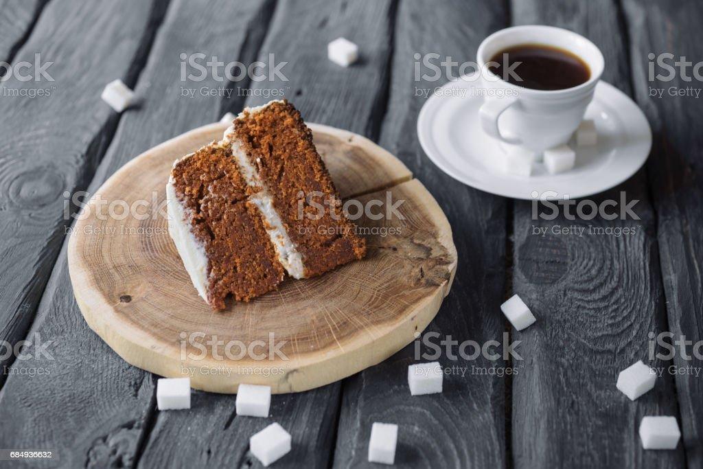 Stück hausgemachten Kuchen und Kaffee auf einem schwarzen Holztisch. Keks-Kuchen mit schwarzen Kaffee. Würfelzucker auf einen Tisch verstreut. Lizenzfreies stock-foto